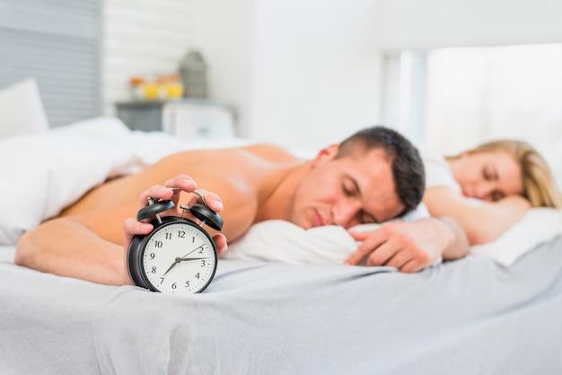 スヌーズの近くのベッドで寝る若いカップル 無料写真