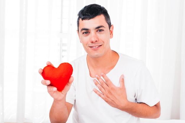 装飾的な心を持っている胸に手で笑顔の男 無料写真