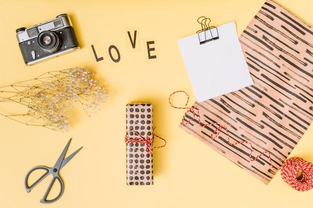 はさみ、カメラ、プレゼントボックス、植物、紙の近くの愛のタイトル 無料写真