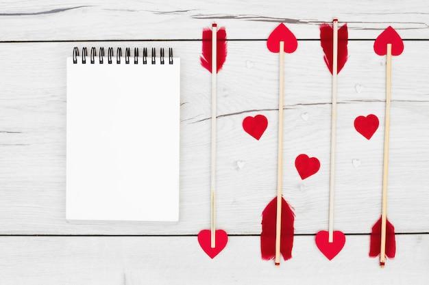 ノートブックの近くに小さな心を持つ杖の装飾羽 無料写真