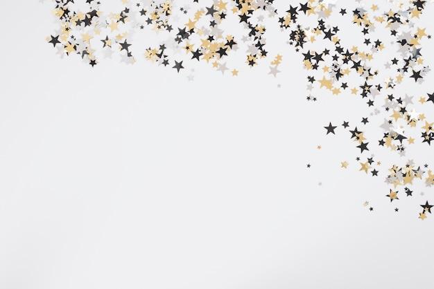 白いテーブルに小さな星のスパンコール 無料写真
