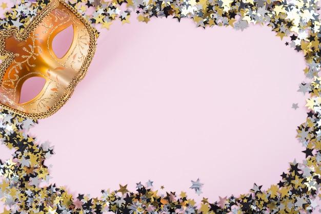 ピンクのテーブルの上に小さなスパンコールのカーニバルマスク 無料写真