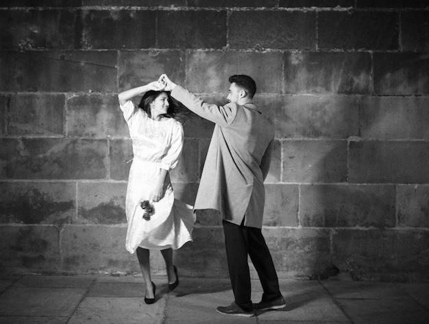 夜の通りで踊っている若いカップル 無料写真