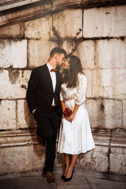 ストリートにキスするエレガントな服の若いカップル 無料写真