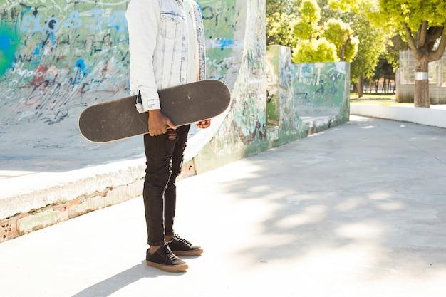 都市環境でスケートボードを持つ男 無料写真