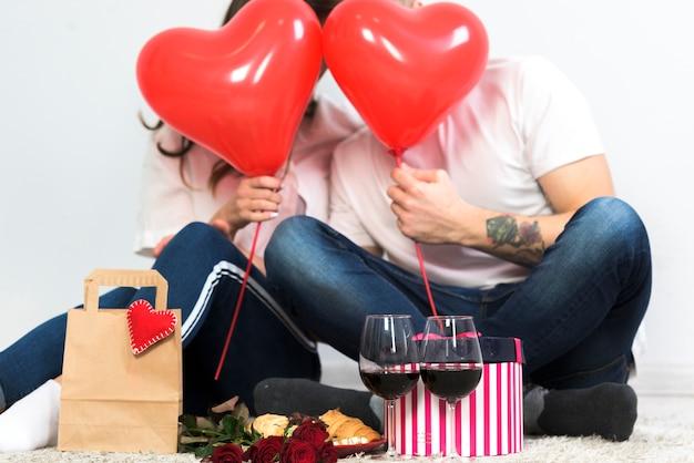 赤い心の風船で顔を覆うカップル 無料写真