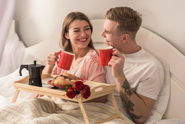 ベッドでコーヒーを飲む若いカップル 無料写真
