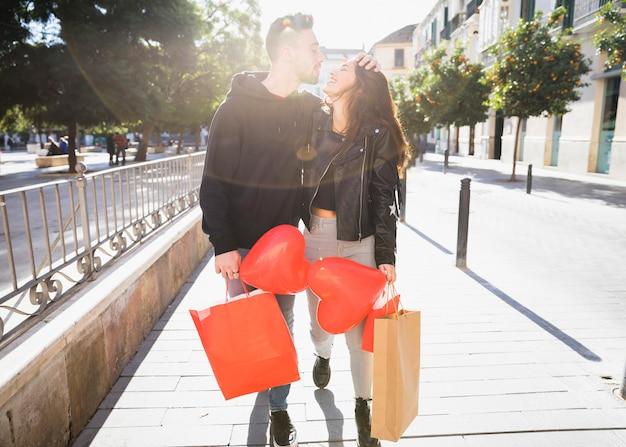 Молодая женщина и улыбающийся человек с пакетами и воздушными шарами на улице Бесплатные Фотографии