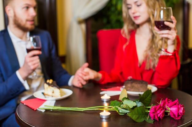 ワインを飲んでテーブルで手をつないでカップル 無料写真
