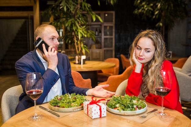 レストランでテーブルに座っている悲しい女性 無料写真
