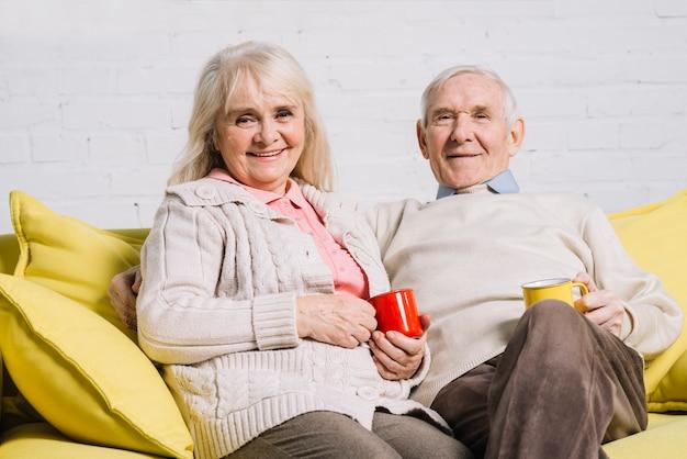 Пожилая пара с кружками кофе Бесплатные Фотографии
