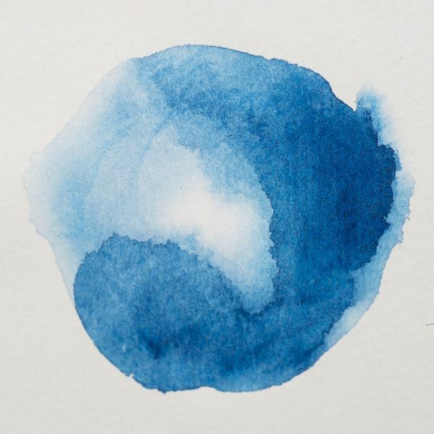 白い紙の上に円形の形の青色の塗料 無料写真