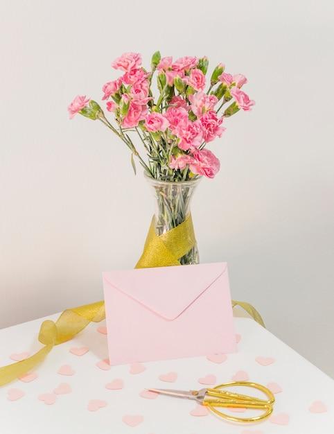 Букет цветов в вазе с лентой возле конверта, ножницы и бумажные сердечки Бесплатные Фотографии