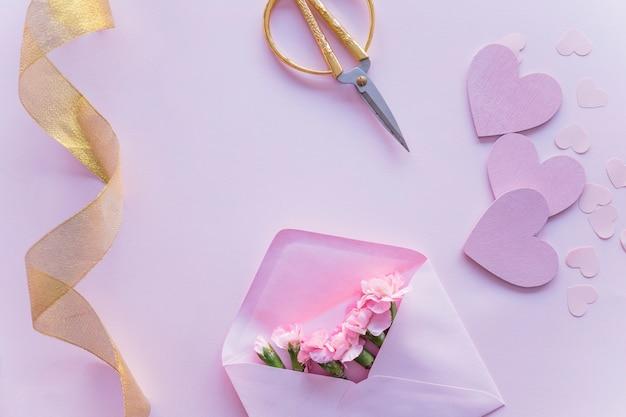 Розовые цветы в конверте с бумажными сердечками на столе Бесплатные Фотографии