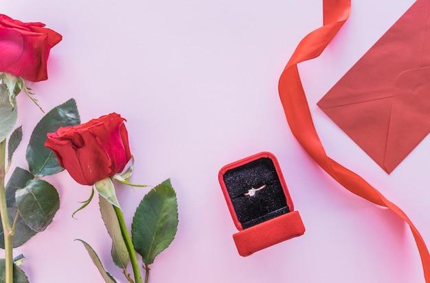 テーブル上のボックスに結婚指輪と赤いバラ 無料写真