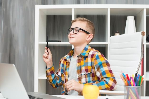 デスクでノートパソコンを持っている男の子 無料写真