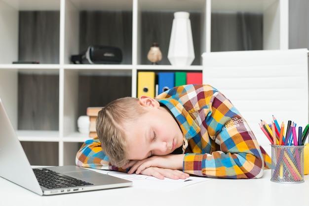 机の上でラップトップの前で眠っている男の子 無料写真