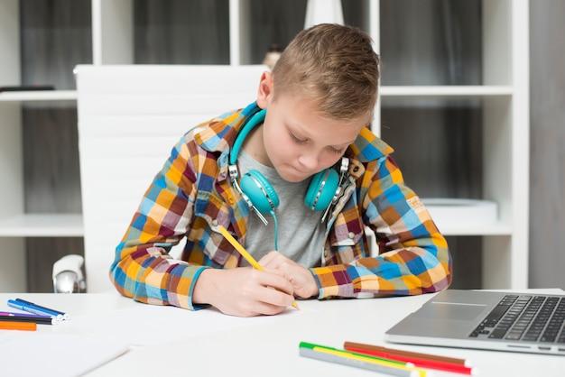 ラップトップで宿題をしている少年 無料写真