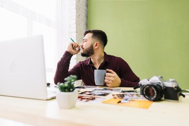 Фотограф пьет кофе на работе Бесплатные Фотографии