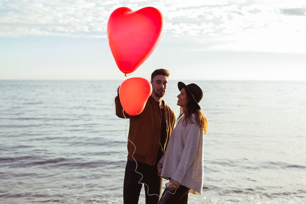 Пара стоит на берегу моря с красными сердечными воздушными шарами Бесплатные Фотографии