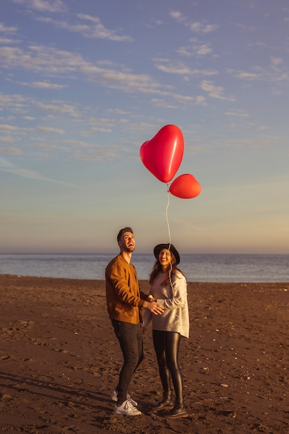 Пара, глядя на летающий сердечный воздушный шар на берегу моря Бесплатные Фотографии