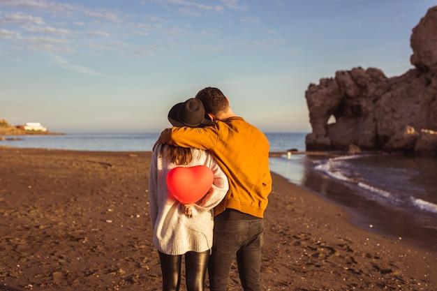 Мужчина обнимает женщину с красным сердцем шар на берегу моря Бесплатные Фотографии