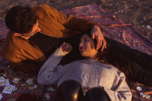 海岸の小物の上に横たわるカップル 無料写真