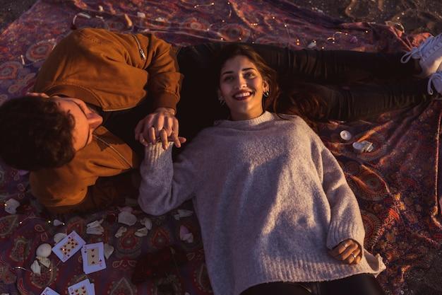 掛け布団の上に横たわる幸せなカップル 無料写真