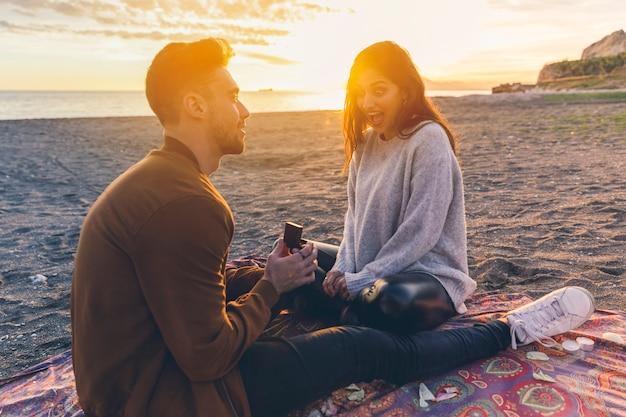 海岸で女性に提案をする男 無料写真