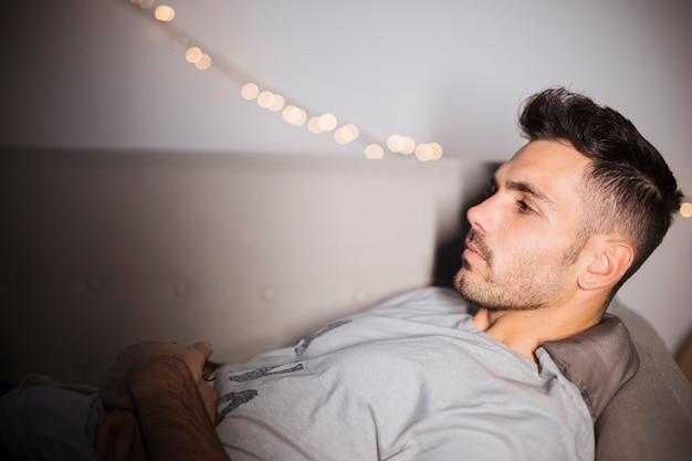 物思いにふける若い男がソファーに横になっています。 無料写真