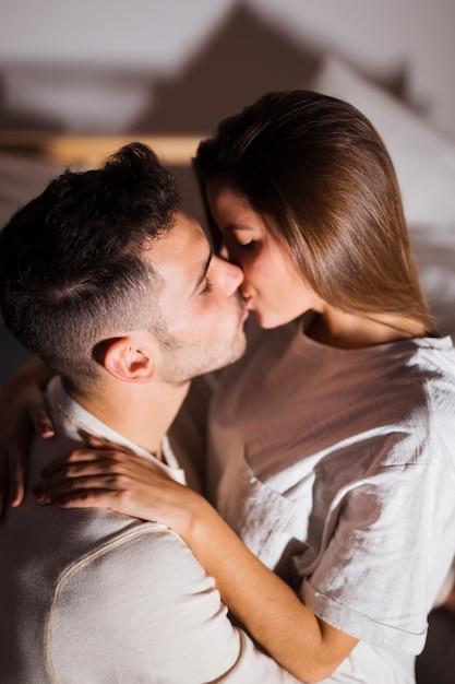 女性と男のキスをし、暗い部屋でベッドにぴったりの 無料写真
