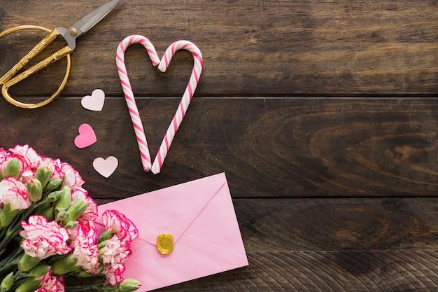 花束、ハサミ、キャンディー・ケインの花束の近くの封筒 無料写真
