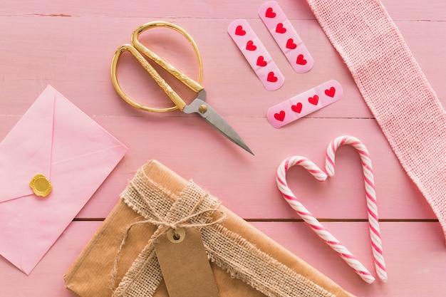 封筒、はさみ、キャンディーの杖の近くの箱 無料写真