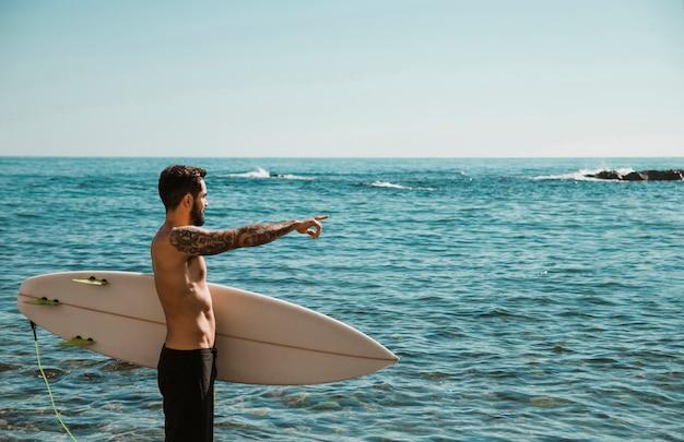 水を指してビーチでサーフボードを持つ若者 無料写真