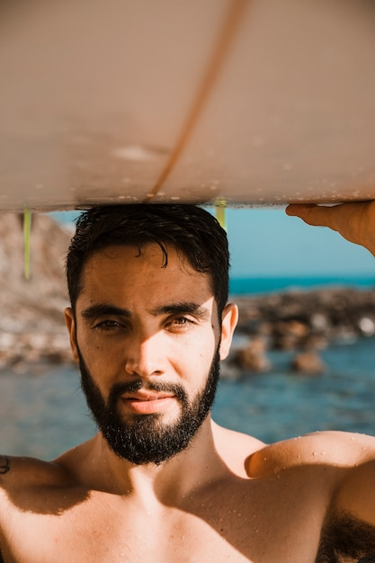 海の近くのビーチで頭の上のサーフボードを持つ若者 無料写真