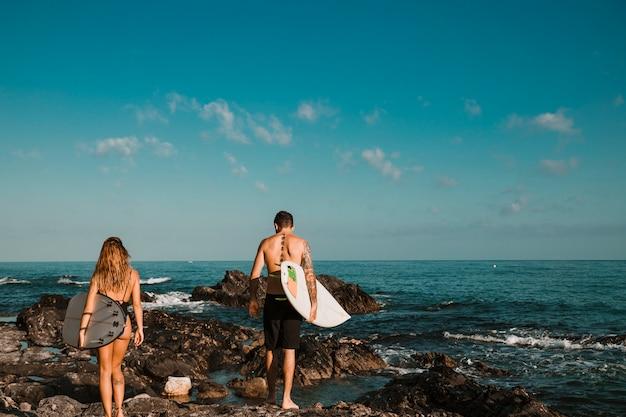 若い男と水に石の海岸に行くサーフボードを持つ女性 無料写真