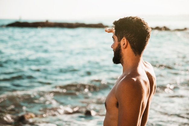 Молодой парень смотрит далеко от воды Бесплатные Фотографии