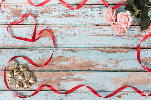 テーブルの上のピンクのバラと小さな心 無料写真