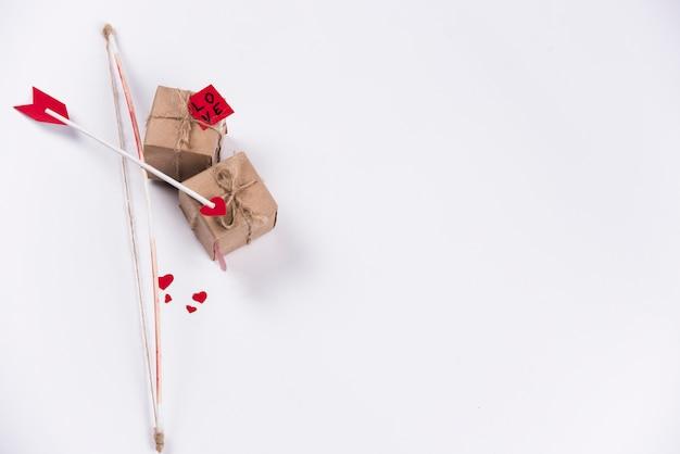 テーブルの上の弓とギフトボックスと愛の矢印 無料写真