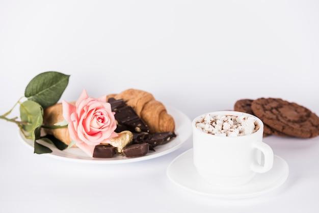 皿の上のバラの花とお菓子 無料写真