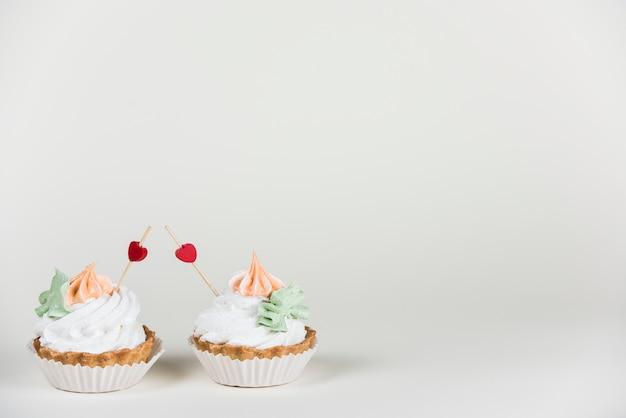 Сердце топперс в двух кексов на столе Бесплатные Фотографии
