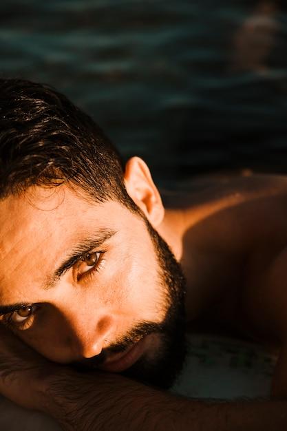 ひげを生やした若い男が水の上に横たわる 無料写真