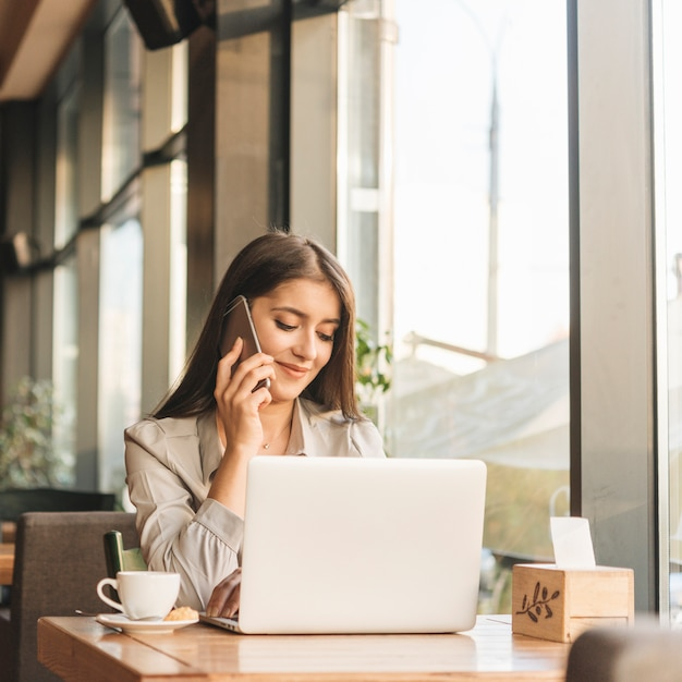 Независимая женщина, работающая с ноутбуком в кафе Бесплатные Фотографии