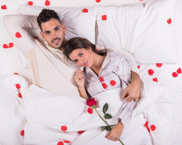 バラの花びらが付いているベッドで横になっているかわいいカップル 無料写真