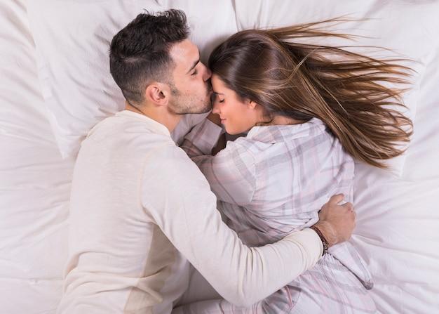 男がベッドの中でおでこに女性にキス 無料写真