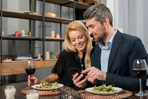 テーブルで陽気な女性にスマートフォンを指している幸せな男 無料写真