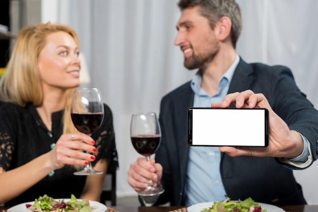 ワインのグラスを持つ女性の近くに笑みを浮かべて男表示スマートフォン 無料写真