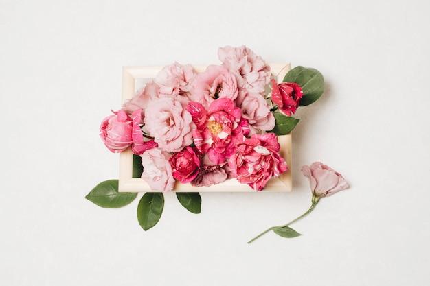 ボックスの葉の近くで新鮮な美しいピンクの花の組成 無料写真