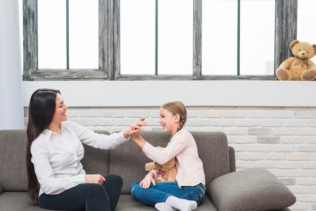 Счастливый женский психолог дает высокие пять для маленькой девочки, сидя на диване у себя дома Бесплатные Фотографии