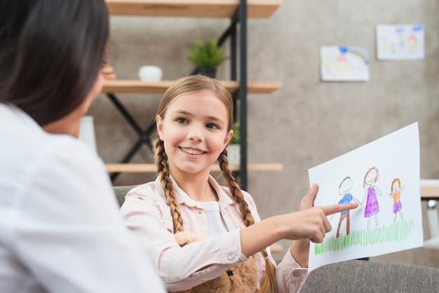 彼女の女性心理学者に描く家族を示す女の子の肖像画を笑顔 無料写真
